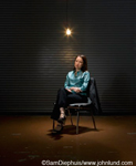 Asian businesswoman sitting under light bulb